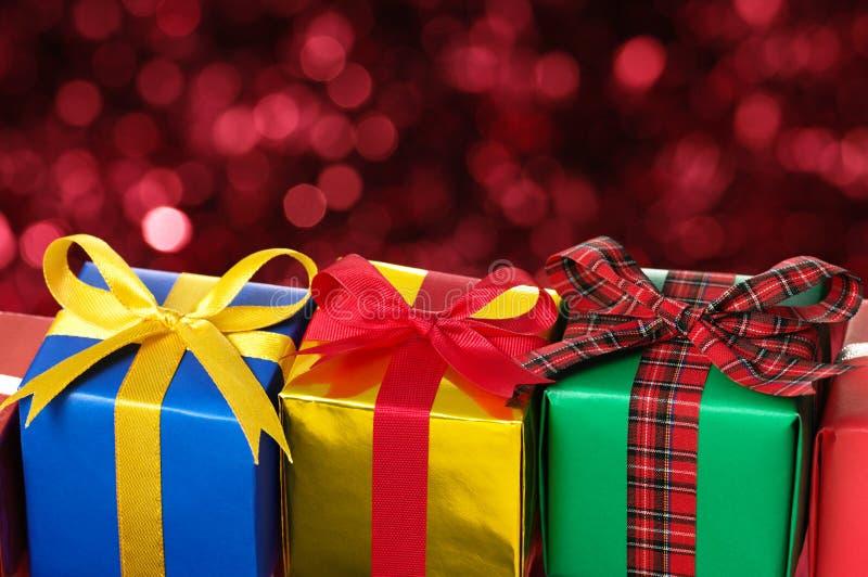 Trois cadeaux sur le fond trouble rouge de lumières. image stock