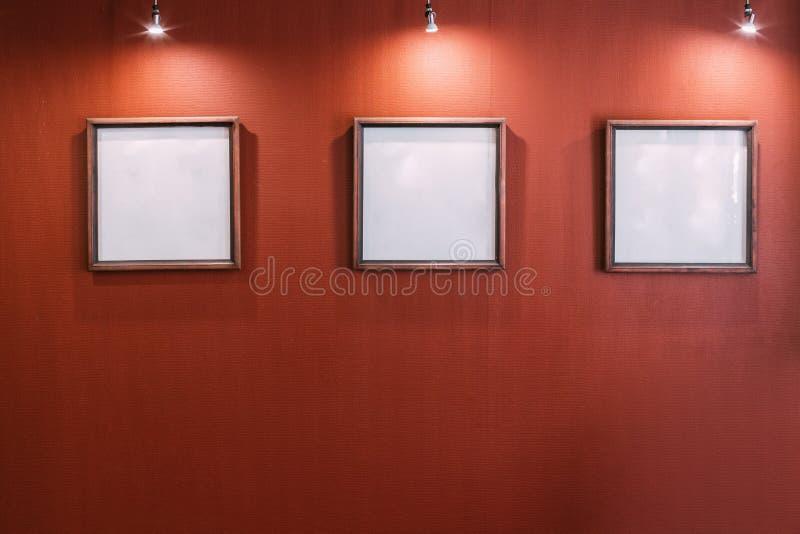 Trois cadres vides blancs sur le mur rouge photo libre de droits