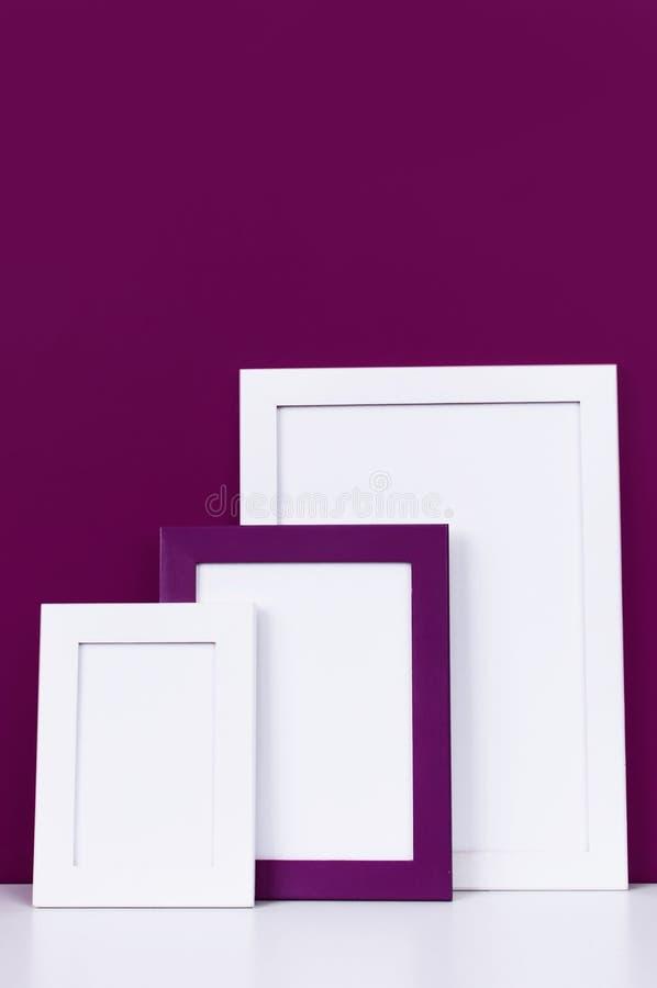Trois cadres vides en bois pour une photo sur une étagère blanche sur un fond d'un mur rouge pourpre lumineux Cadres de papier bl images stock