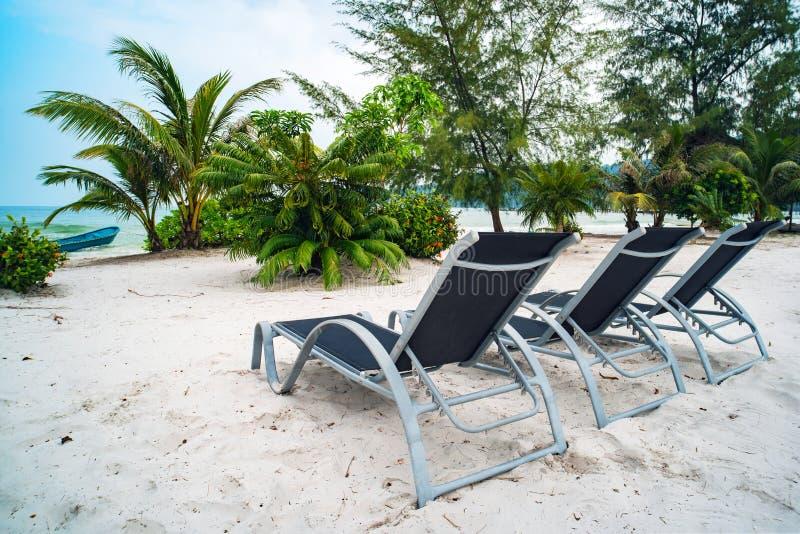 trois canap?s du soleil se tiennent sur le sable blanc contre le ciel bleu et la mer claire avec de l'eau turquoise Le concept de photographie stock