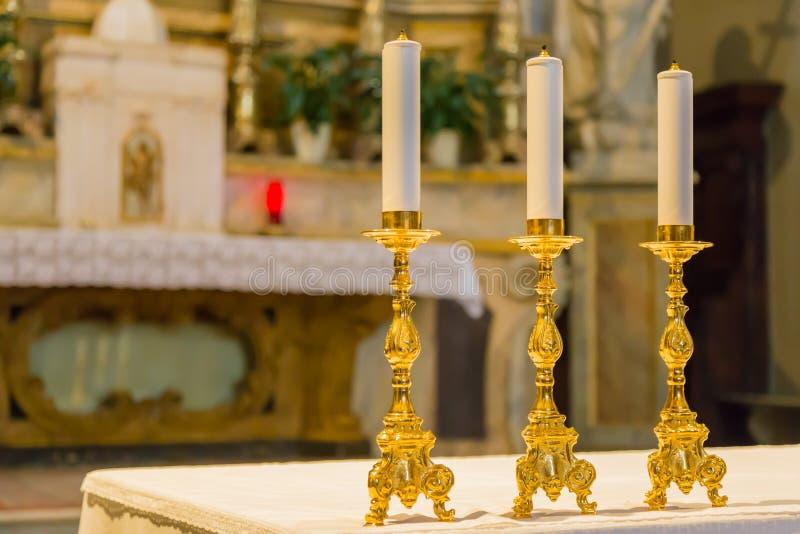 Trois candélabres sur l'autel de l'église images stock