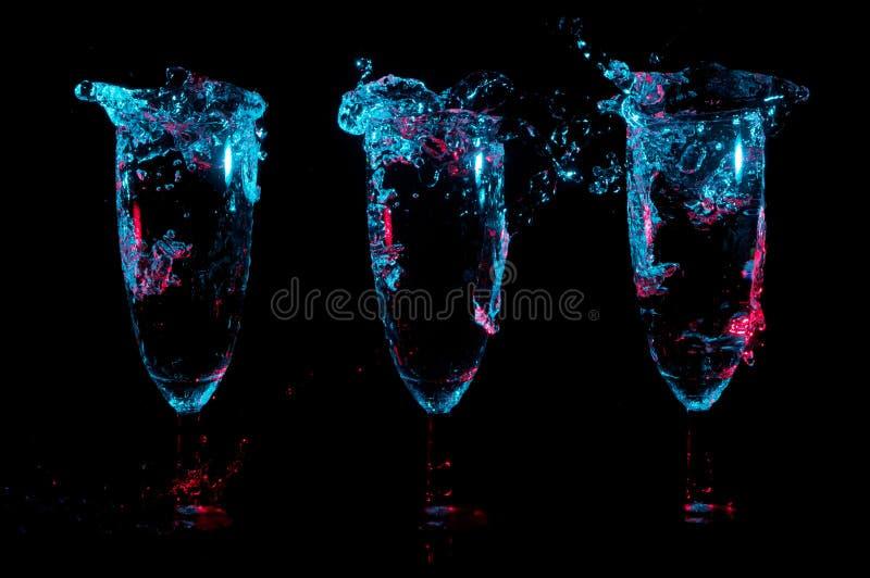 Trois cannelures de champagne avec grand éclabousse sous les lumières bleues des points culminants rouges sur un fond noir images libres de droits