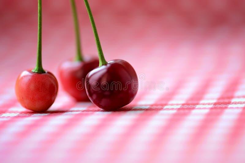 Trois cerises rouges sur une table photographie stock