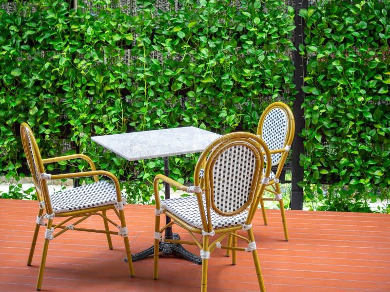 Trois chaises blanches en bois de cru avec la table de marbre blanche sur le plancher rouge sur le fond vert d'usine de lierre photos stock