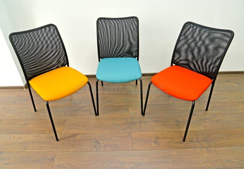 Trois chaises de bureau avec des sièges de couleur se tiennent à l'intérieur photographie stock libre de droits