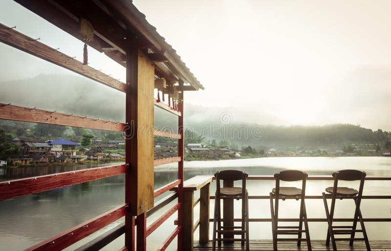 Trois chaises en bambou sur un beau lac au temps de matin images stock