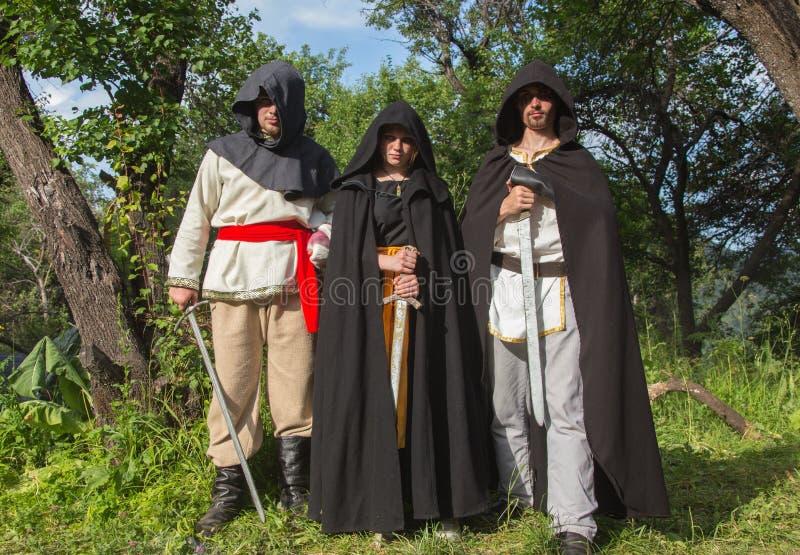 Trois chevaliers dans l'armure combat à la forêt images stock