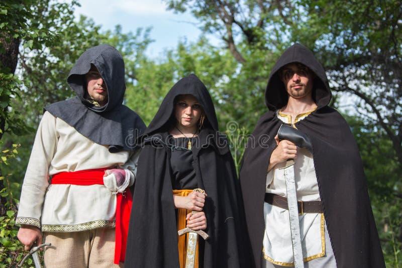 Trois chevaliers dans l'armure combat à la forêt photographie stock