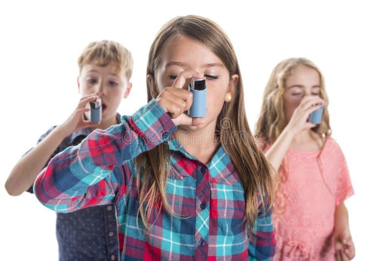 Trois childs utilisant l'inhalateur pour l'asthme Fond blanc image stock