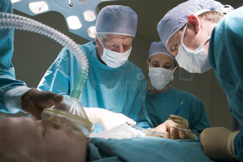 Trois chirurgiens fonctionnant sur un patient photo libre de droits