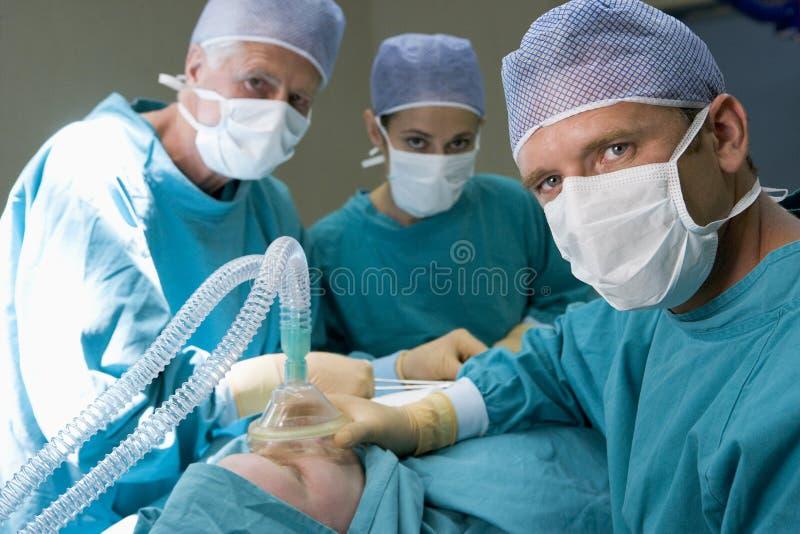 Trois chirurgiens fonctionnant sur un patient images libres de droits