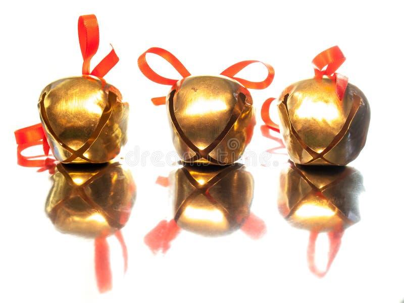 Trois cloches de traîneau avec les arcs rouges de ruban photo libre de droits