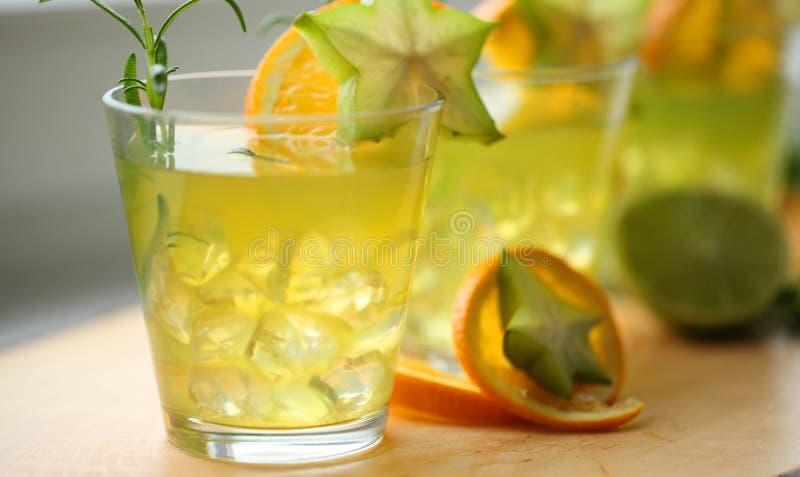 Trois cocktails de glace de vert jaune se tenant sur le bois, décoré de l'orange, du carambolier, de la chaux et du romarin Prépa photos libres de droits