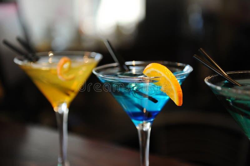 Trois cocktails sur la barre jaune, bleu, vert Décoré d'une tranche de citron photo libre de droits