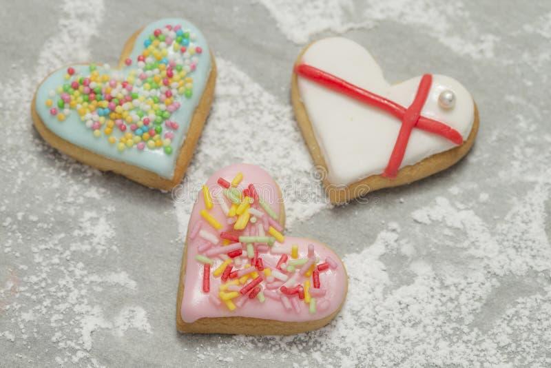 Trois coeurs de la valentine cuite au four sur le fond en poudre photo stock