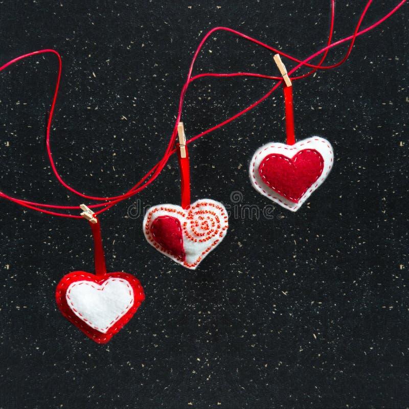 Trois coeurs de tissu sur un fond noir Symbole de l'amour photos stock