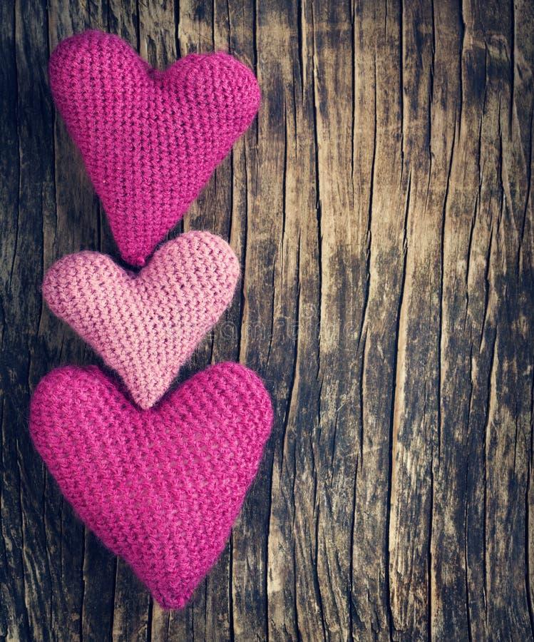 Trois coeurs roses de crochet sur le fond en bois photo stock