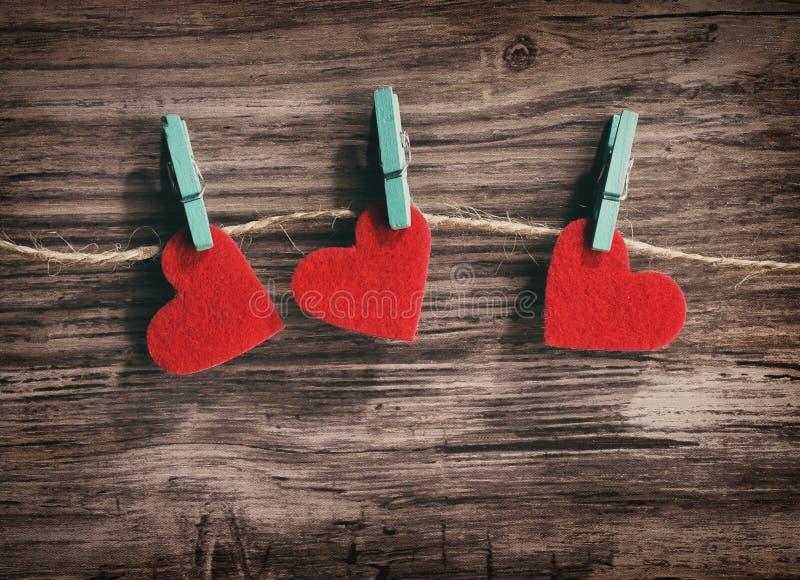 Trois coeurs rouges accrochant sur une corde sur un fond en bois photographie stock