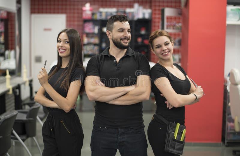 Trois coiffeurs posant dans le salon de coiffure image stock