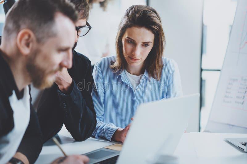 Trois collègues au processus fonctionnant Jeune femme collaborant avec le collègue au bureau moderne Concept de travail d'équipe images stock