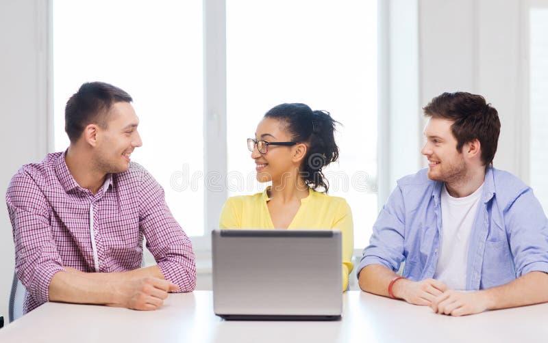 Trois collègues de sourire avec l'ordinateur portable dans le bureau image stock