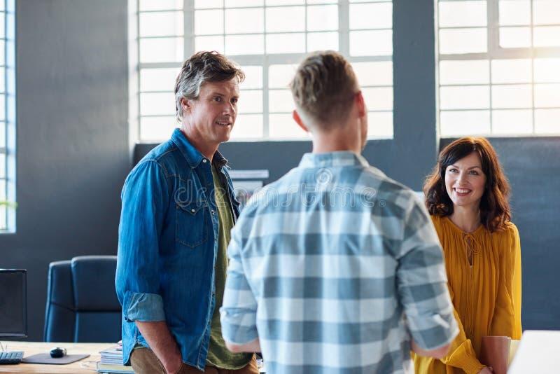 Trois collègues de sourire parlant ensemble dans un bureau moderne images stock