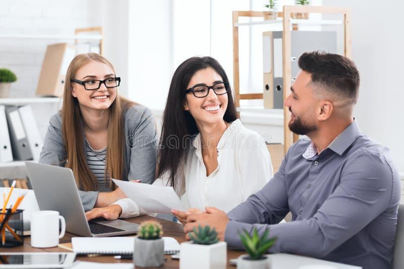 Trois collègues discutant le projet au bureau moderne image stock