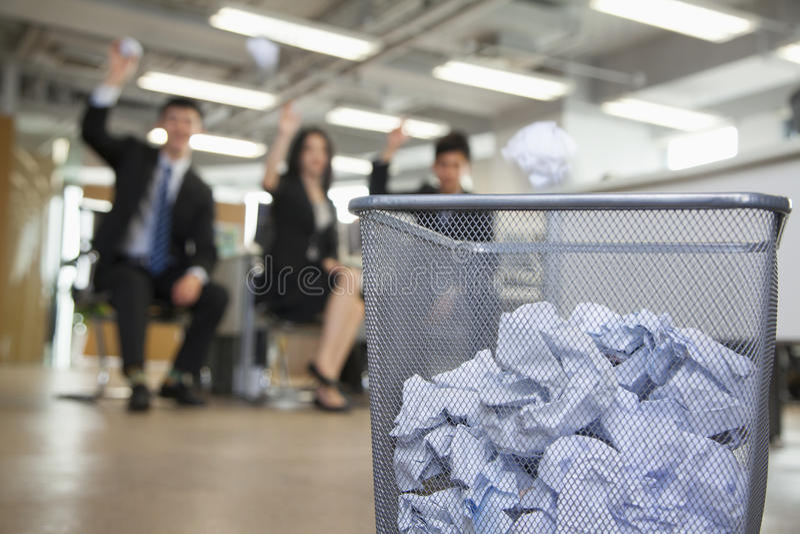Trois collègues disposant à jeter le papier dans le panier de rebut photos libres de droits
