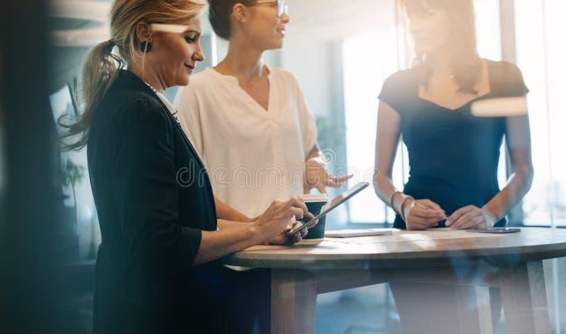 Trois collègues féminins ayant une réunion debout images stock