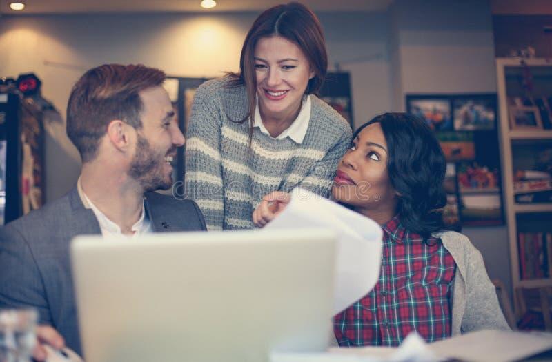 Trois collègues travaillant ensemble sur l'ordinateur portable images stock