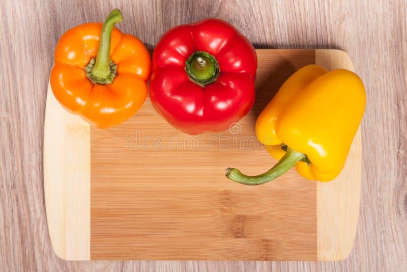 Trois couleurs les poivrons sur le fond en bois de coupe Poivrons jaunes, oranges et rouges Poivre populaire dans la cuisine photographie stock
