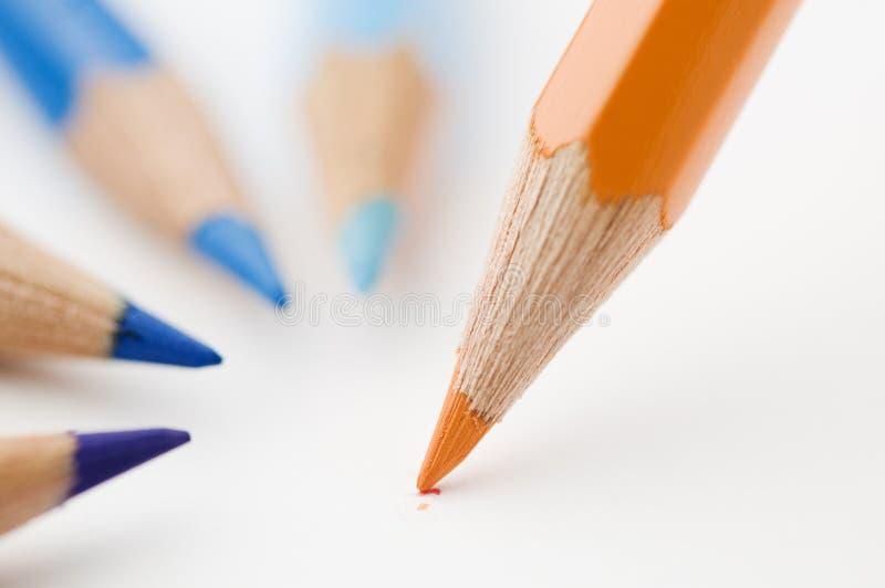Trois crayons bleus et d'une orange photo stock