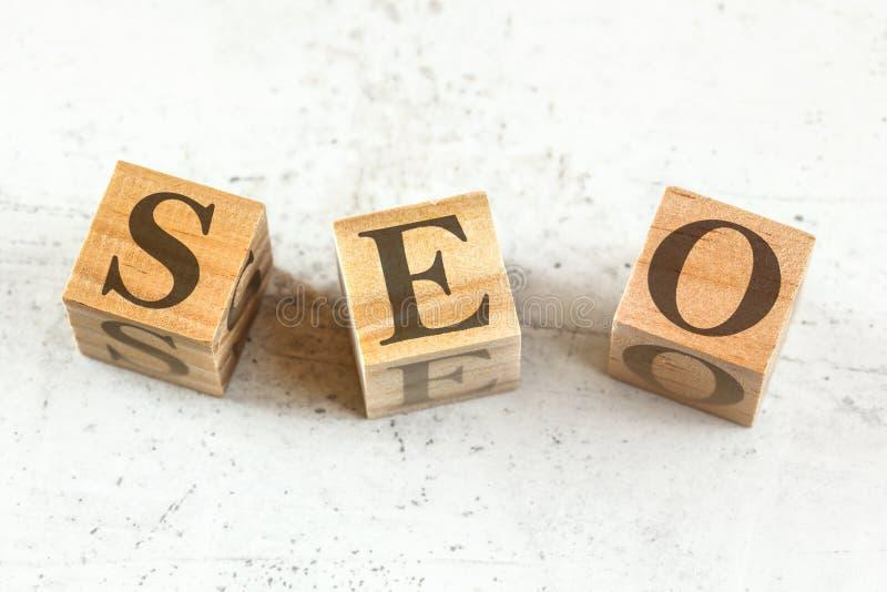 Trois cubes en bois avec les lettres SEO représente l'optimisation de moteur de recherche sur le conseil blanc images libres de droits