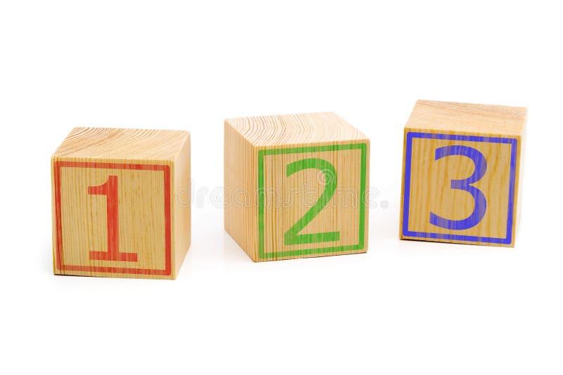 Trois cubes en bois bruns ont aligné dans une rangée avec des numéros un, deux image libre de droits