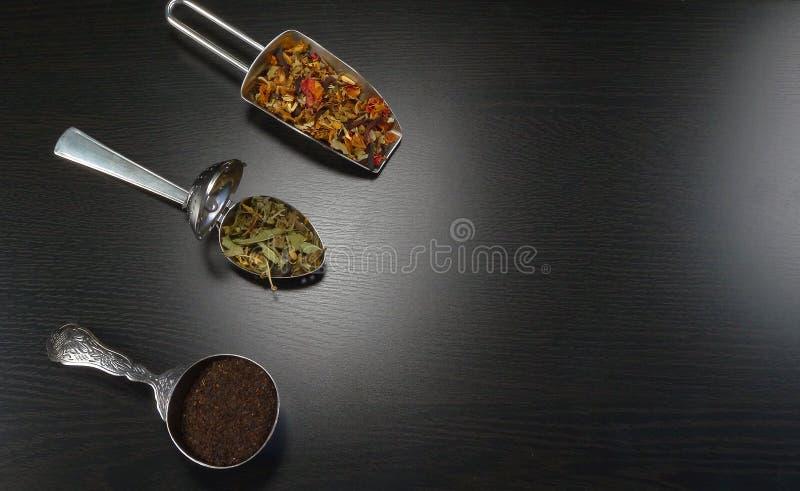 Trois cuillères de thé avec le vrai thé sur un fond en bois noir image stock
