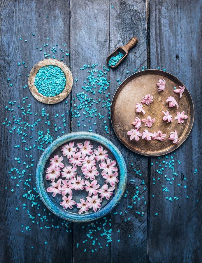 Trois cuvettes avec les fleurs, le sel de mer et le scoop sur la table en bois bleue, fond de bien-être photographie stock libre de droits