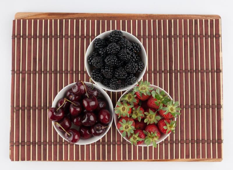 Trois cuvettes en céramique avec des baies - fraises, mûres, a photographie stock libre de droits