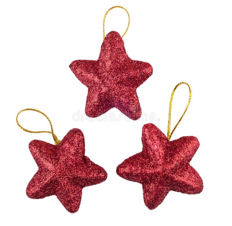 Trois décorations rouges de Noël d'étoiles sur le blanc photographie stock libre de droits