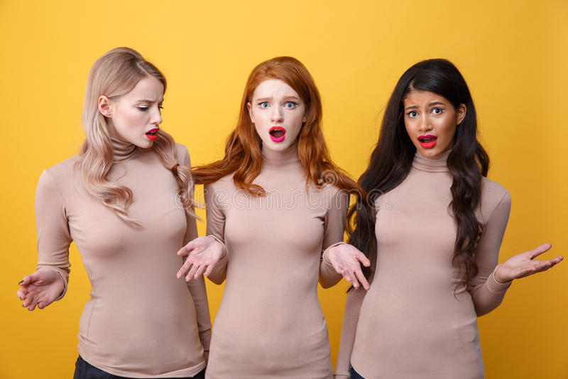 Trois dames confuses se tenant avec les cheveux attachés photo stock