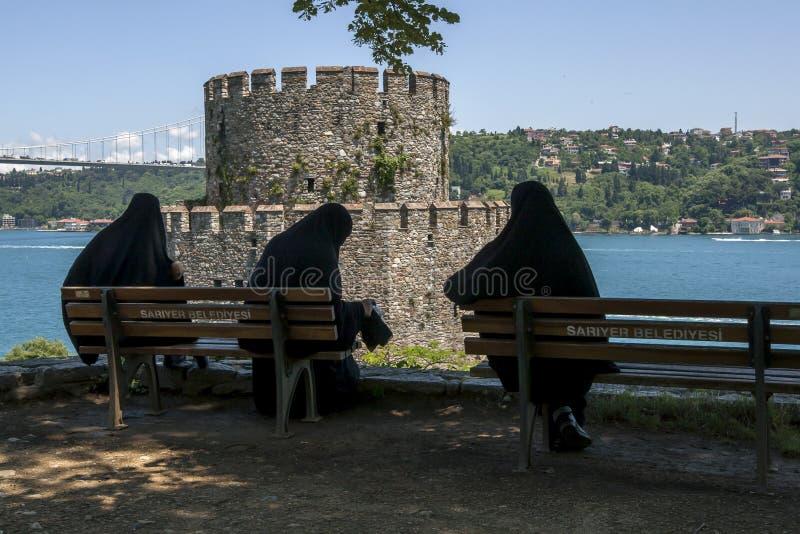 Trois dames musulmanes s'asseyent devant Halil Pasha Tower chez Rumelhisarii à Istanbul en Turquie photographie stock