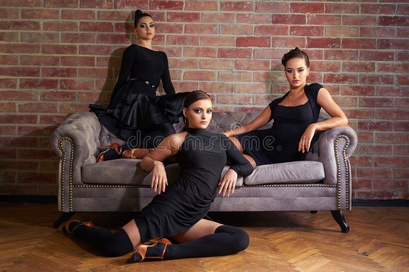 Trois danseuses latines élégantes de femmes dans des robes noires posant près du sofa photos libres de droits