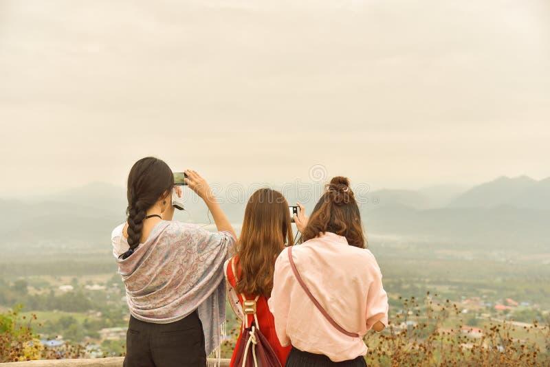 Trois de dames asiatiques apprécient le Mountain View, emploient le captur futé de téléphone images stock