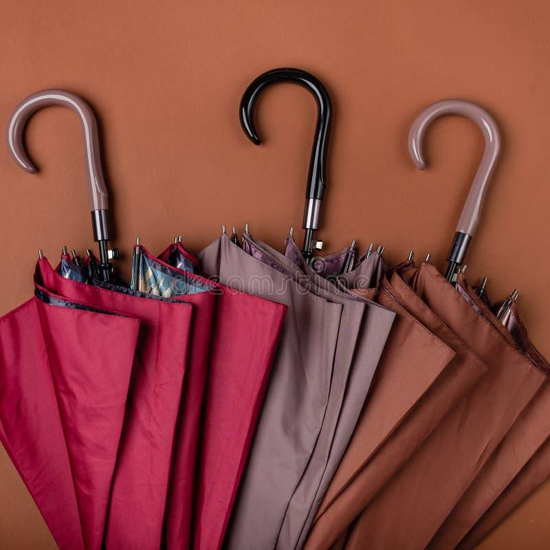 Trois de parapluies colorés stockés à l'arrière-plan brun image stock