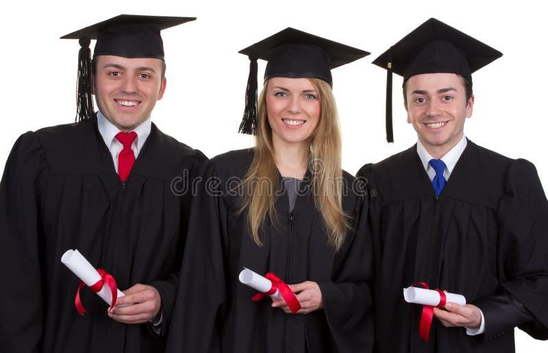 Trois diplômés avec des rouleaux souriant et d'isolement sur le blanc images libres de droits