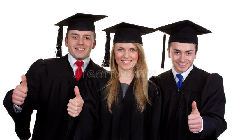 Trois diplômés avec pouces vers le haut du signe, d'isolement sur le blanc photo libre de droits