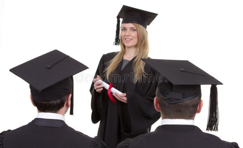 Trois diplômés, une position devant les autres deux, isolat photos libres de droits