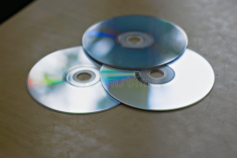 Trois disques compacts sur le bureau image libre de droits
