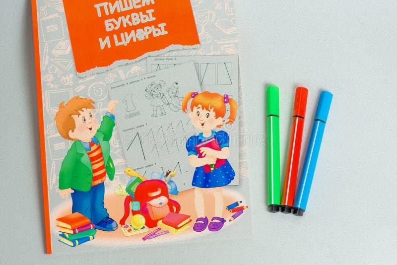 Trois du marqueur se trouvant à côté d'un carnet pour des écoliers, colorant illustration libre de droits