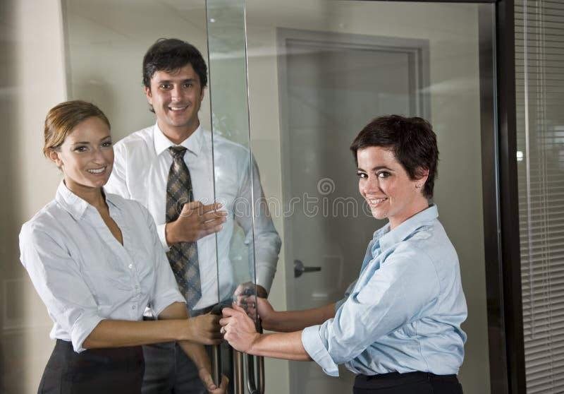 Trois employés de bureau à la trappe de la salle de réunion images libres de droits