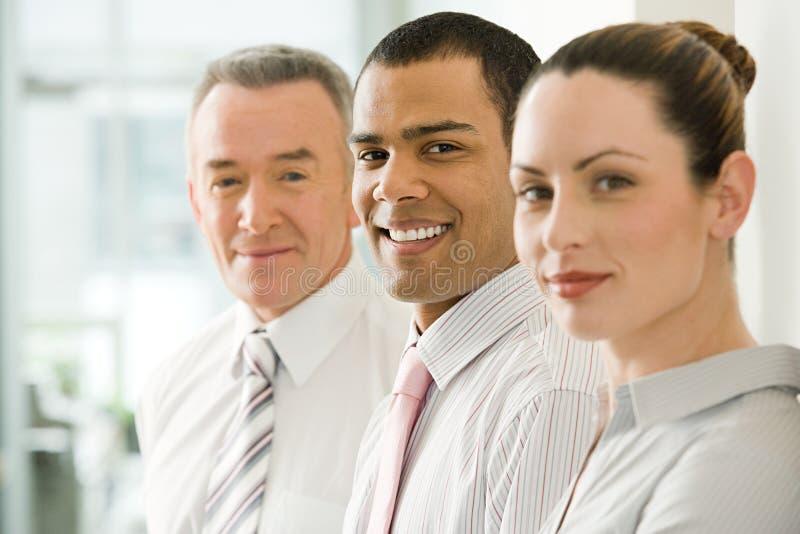 Trois employés de bureau dans une rangée images libres de droits